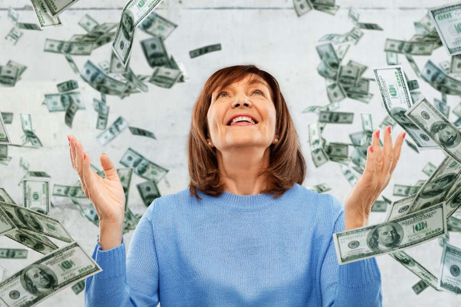 Senior woman in a blue sweater watching money fall around her head